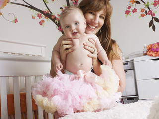 Mother holding baby girl in tutu