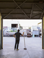 Worker holding broom in warehouse