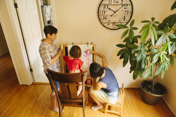 Caucasian family drawing on easel