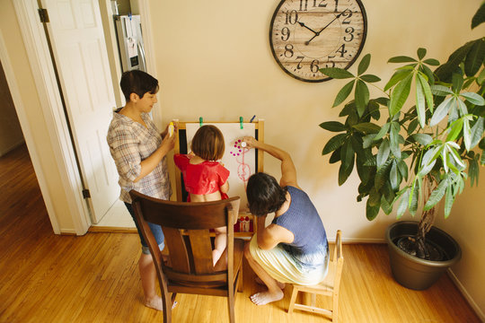 Family drawing on easel at home