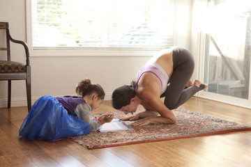 Woman practicing yoga and helping daughter with homework