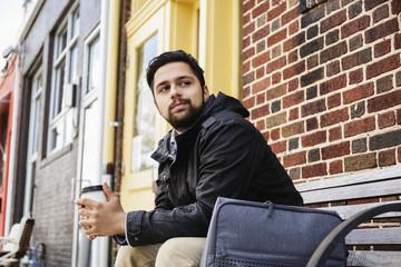 Hispanic man sitting on city bench drinking coffee