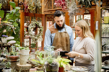 Caucasian employees using digital tablet in plant nursery