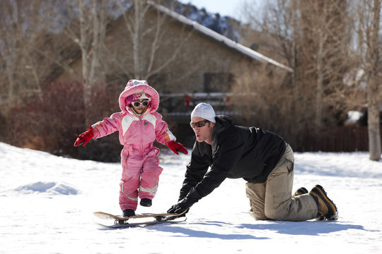 Father and daughter playing in snow