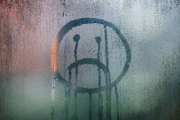 Sad upside down smiley hand drawn symbol on wet glass background.