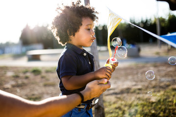 African american baby blowing soap bubbles in the park.