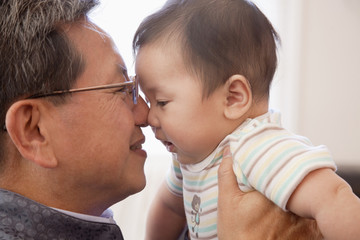 Grandfather giving Chinese grandson Eskimo kiss