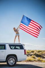Hispanic woman waving American flag on roof of white SUV