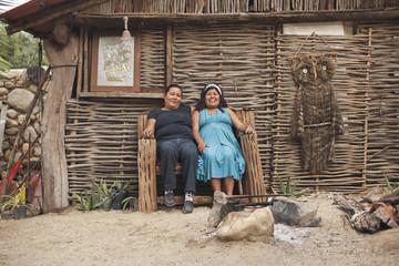 Hispanic women sitting in front of house