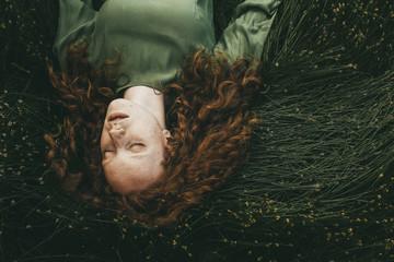 Caucasian girl sleeping in grass