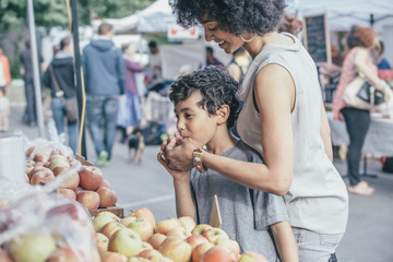 Mixed race boy shopping with mother at farmers market