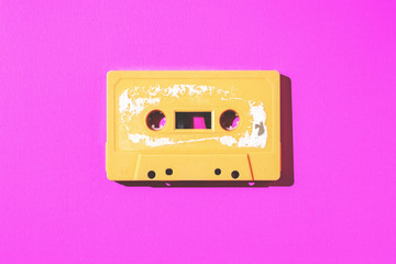 Old cassette tape on pink paper with copy space