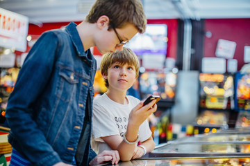 Caucasian brothers using cell phone in arcade