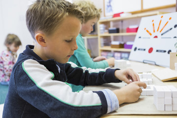 Close up of boy solving puzzle in classroom