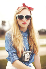 Caucasian woman wearing sunglasses and instant camera
