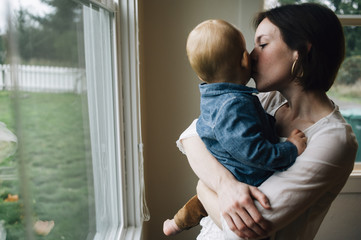 Mother kissing son at window