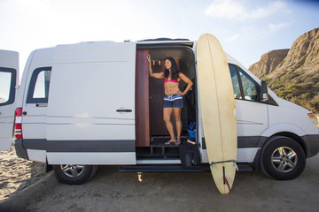 Hispanic surfer standing in van with surfboard