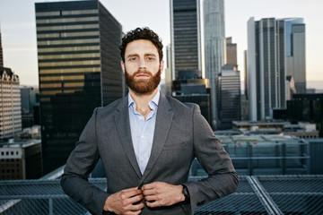 Caucasian businessman buttoning jacket on urban rooftop