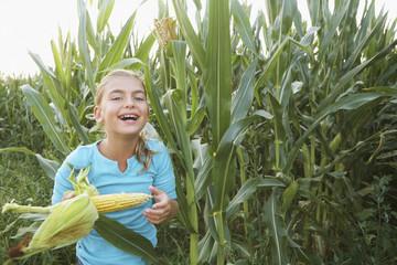 Caucasian girl eating corn in field