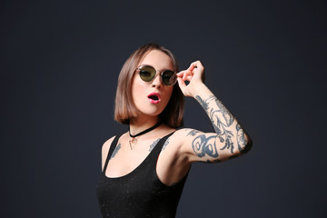 Beautiful young woman with tattoo wearing sunglasses and posing on black background
