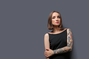 Beautiful young woman with tattoo posing on gray background