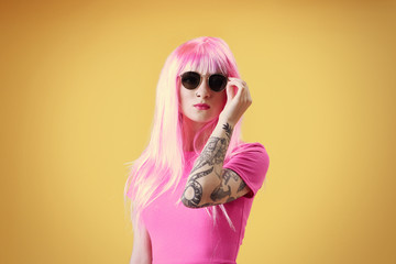 Beautiful young woman with tattoo wearing pink wig and sunglasses on yellow background
