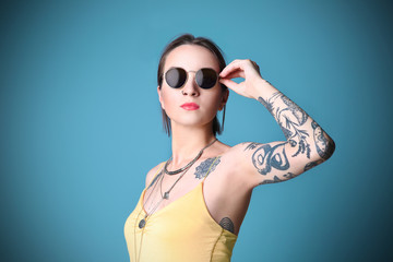 Beautiful young woman with tattoo wearing sunglasses and posing on blue background