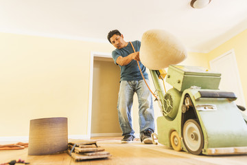 Hispanic man refinishing floors in new house