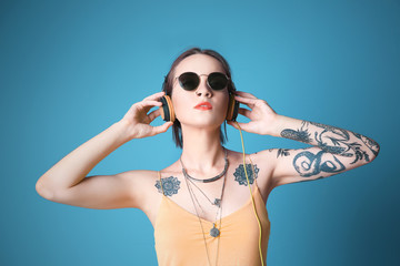 Beautiful young woman with tattoo wearing sunglasses and headphones on blue background