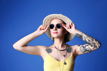 Beautiful young woman with tattoo wearing hat and sunglasses on blue background