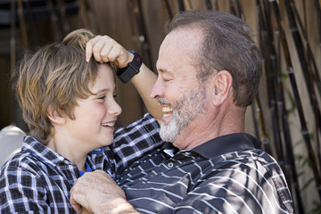 Older Caucasian man relaxing with grandson outdoors