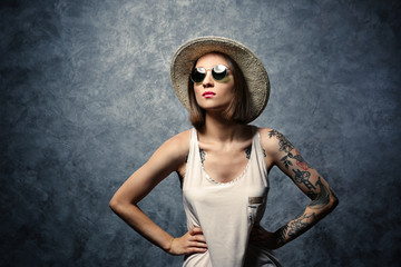 Beautiful young woman with tattoo wearing sunglasses and hat on gray background