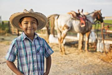Hispanic boy smiling on ranch