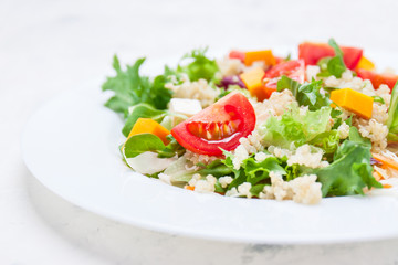 Homemade autumn healthy salad with quinoa, salad leaves, tomatoes, pumpkin and feta cheese on a white plate, closeup, selective focus