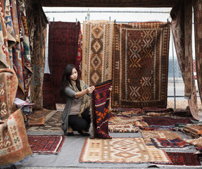 Chinese woman shopping for rugs in flea market