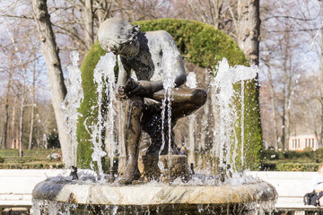 Marble boy sitting in middle of fountain