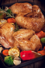 Roasted chicken with vegetables on baking plate