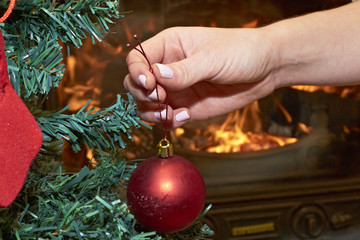 Woman placing ball on Christmas tree with fireplace background