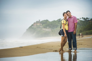 Hispanic couple hugging in waves on beach