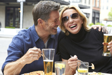 Caucasian couple drinking and eating at sidewalk cafe