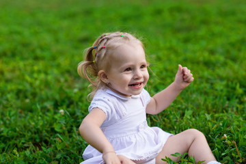 Baby girl in white dress sits and smiling on the fresh green grass