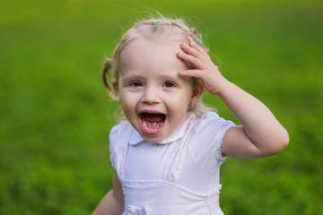 very emotional little girl walks in the summer park
