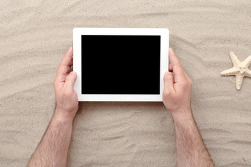 Man holding tablet with blank screen lying on sand