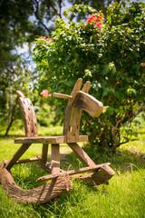 Wooden horse in lush tropical garden in summer