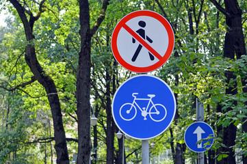 """Дорожные знаки """"Движение пешеходов запрещено"""" и """"Велосипедная дорожка"""" в городском парке"""