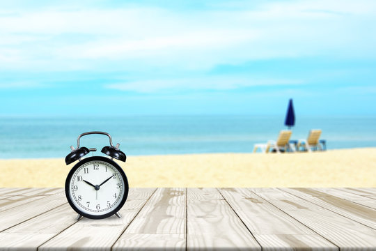 Alarm clock on wood table and sea beach blurred in background