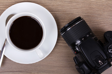 Coffee cup and camera on a wooden surface