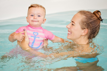 Group portrait of white Caucasian mother and baby daughter playing in water diving in swimming pool inside, looking in camera, training to swim, healthy active lifestyle