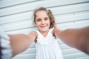 Girl makes a selfie with a smile . She is dressed in a white summer dress