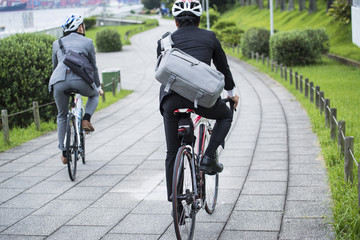 Two businessmen are riding on the road bike in the park wearing a helmet